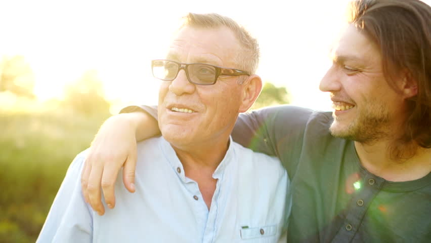 Father and adult son embrace. Close up portrait of a son kisses his father and he strokes his head. Father's Day