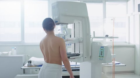 In the Hospital, Back View Shot of Topless Female Patient Undergoing Mammogram Screening Procedure. Healthy Young Female Does Cancer Preventive Mammography Scan. Shot on RED EPIC-W 8K Camera.