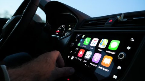 Majorca, Spain - Circa 2018: Home screen of Maps app on Apple CarPlay iOS display screen multimedia device in Seat sporty car driven beautiful woman - co-pilot press touchscreen to see positioning gps