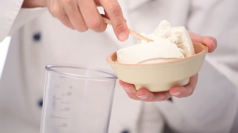 A woman chef puts fresh ricotta in a receptacle. The chef takes ricotta from the bowl and puts a piece of it in a bowl with a wooden spoon