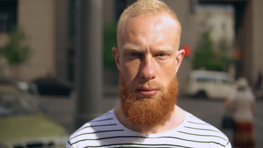 Portrait bearded guy in city standing on the sidewalk looking at the camera. on the background driving cars pedestrian stopped at a red traffic light | Shutterstock HD Video #1012093523