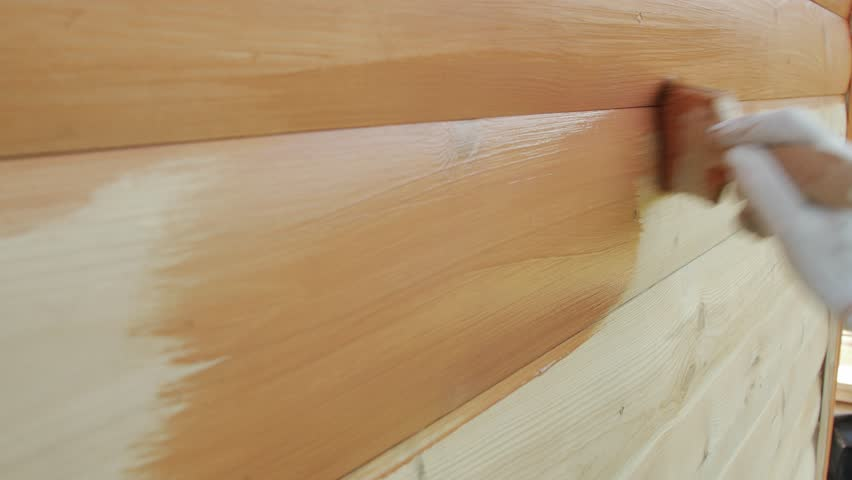 Close up of wood painting with a brush with the brown color.