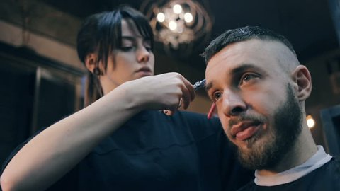 Men's hairstyling and haircutting in a barber shop or hair salon. Grooming the hair. Barbershop. Woman hairdresser doing haircut adult men in the men's hair salon. Haircutter in the workplace