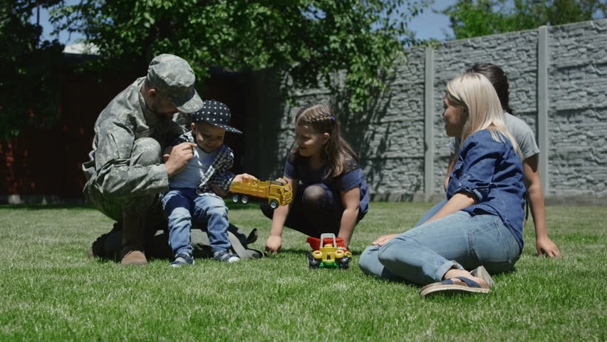Adult man wearing military uniform and having fun with kids and wife in backyard in summertime