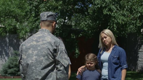 Woman with children saying farewell to man before leaving family and home and going to serve in army
