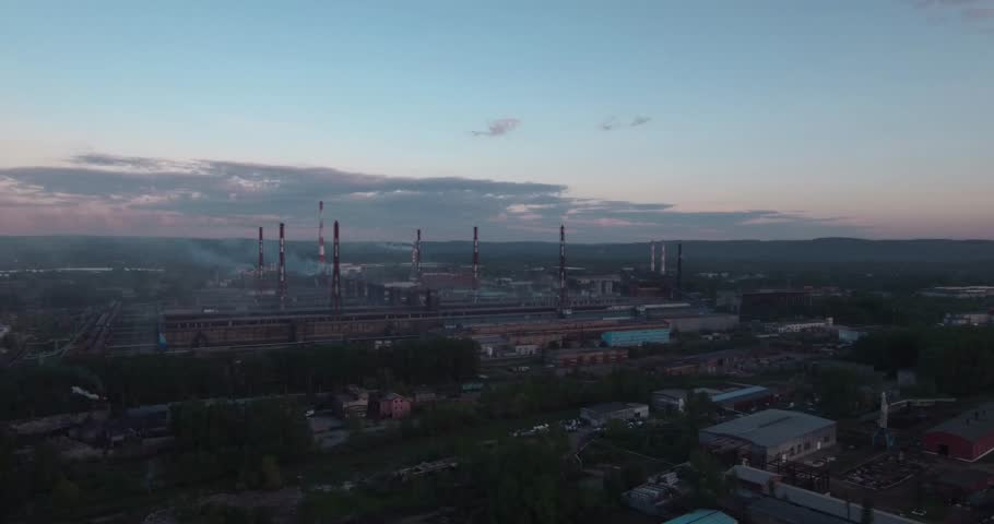 Top view, AERIAL: highway and industrial plant. Air pollution from industrial plants. Pipes throwing smoke in the sky at sunset