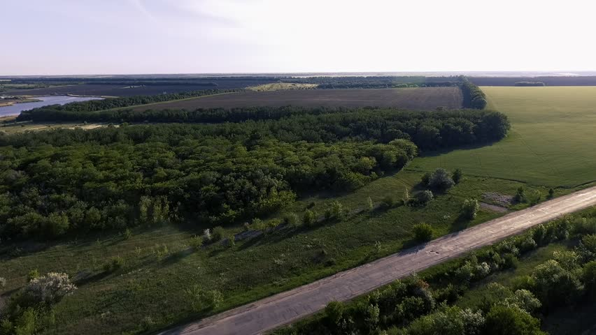 Flight over the fields and the old road with the traveling cars at sunset. Spring season outside the city. Ukraine. Europe.   Shutterstock HD Video #1012127723