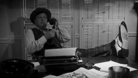 A 1940s newspaper reporter with his shoes on the desk talking on the phone. 51729e507