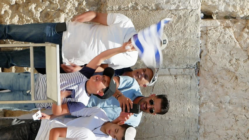 Jerusalem, Israel - May 25, 2017: Israeli family is singing and being happy celebrating the Jerusalem Day near Western Wall or Wailing Wall or Kotel the sacred place for all jews. Vertical video.