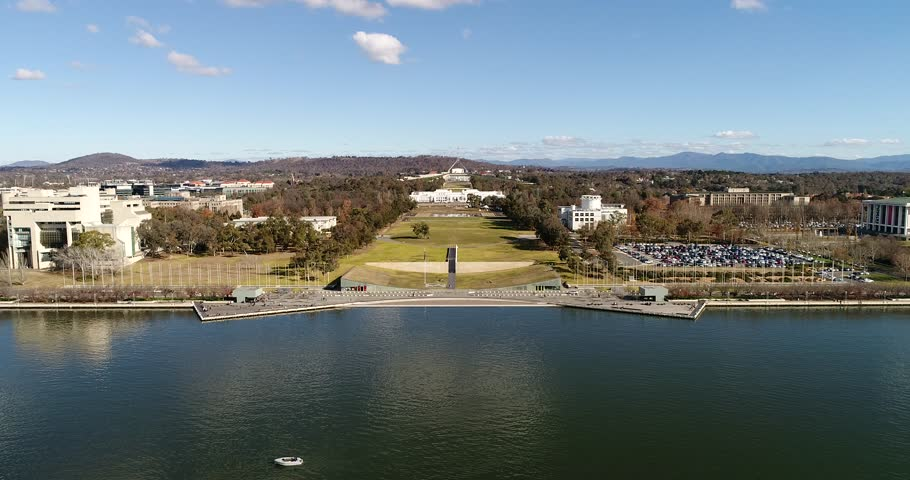 New Australian parliament on capitol hill in Canberra from lake Burley griffin waterfront to grass lawn avenue on a sunny day.