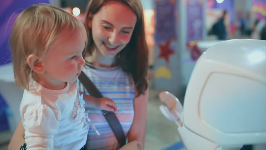 Young mother and her baby is talking to a robot. slow-motion. Modern Robotic Technologies.