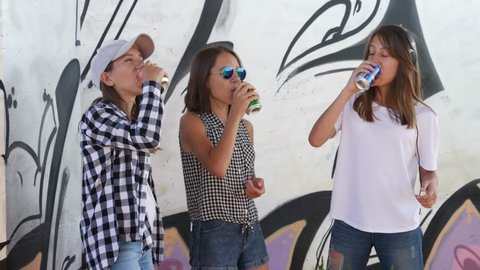 Sisters triple twins teenager girls hang out under bridge drink carbonated can drinks near graffiti wall