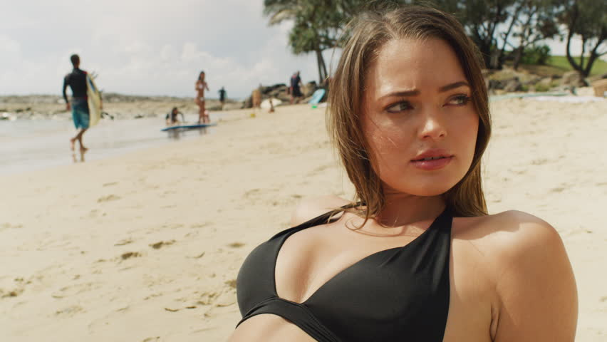 Hot girl lying on beach in the sun. Shot with a RED camera. 4k footage.