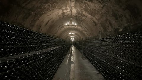 Wine Cellars of the Winery. Old Bottles with Champagne are Kept in Racks. Stone Arches Covered with Mold