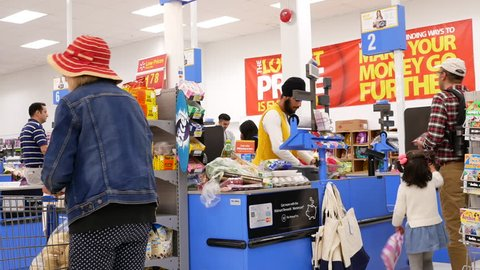 Coquitlam, BC, Canada - May 31, 2018: Motion of people paying foods at check out counter inside Walmart store with 4k resolution