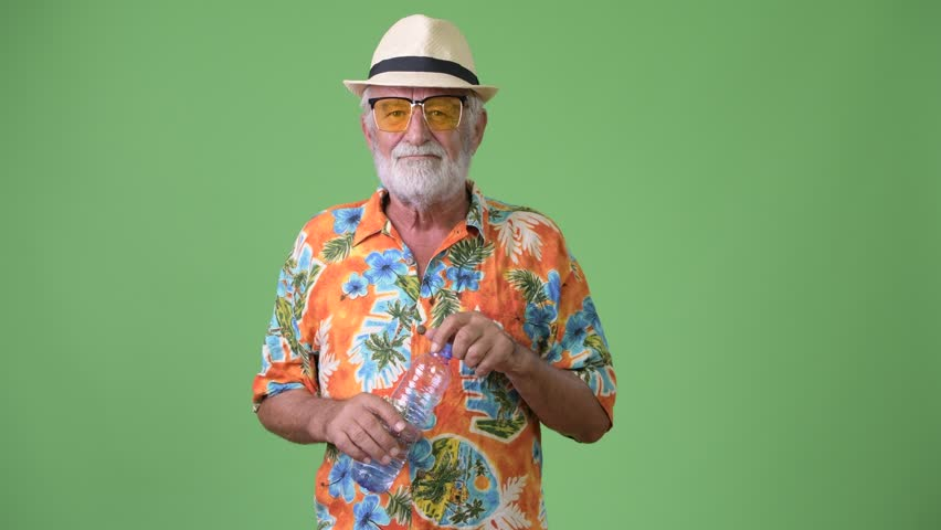 Handsome senior bearded tourist man ready for vacation against green background | Shutterstock HD Video #1012195403