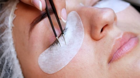 beauty saloon. close-up, procedure for eyelash extension. The master glues each cilium with special glue, works by means of two tweezers
