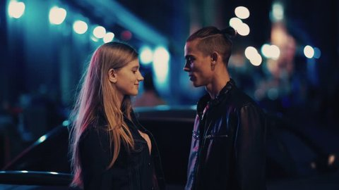 Close up portrait of beautiful young couple kissing at night city street at colorful lights background. Love story, romantic atmosphere, true feelings. Happy together.