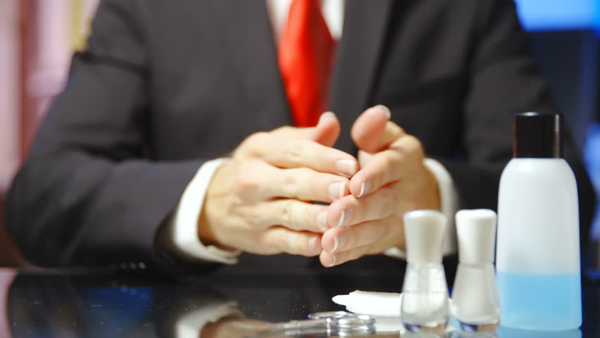 Businessman check hands with long nails in slow motion 4K. Static shot of headless male person both hands in focus with long nails and manicure tools on the right side of the frame.