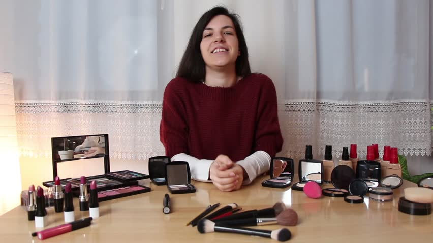 Woman doing make up vlog. Young brunette female doing a video blog about cosmetic products in her home.