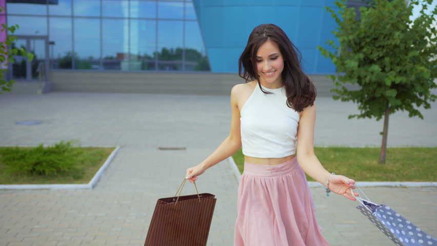 Active attractive girl dances near a shopping center with full of purchases shopping bags