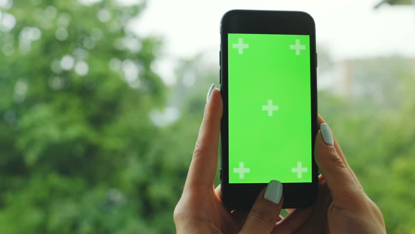 Close-up view of female hand holding smart phone cellphone with empty green screen with cloudy rainy day on blurred background | Shutterstock HD Video #1012222793