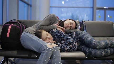 The mother and daughter in the waiting room of the airport sleeping on chairs