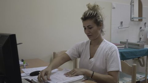 Portrait of pretty blonde nurse in white uniform while sitting and working with patient documentation in ambulatory room at hospital, young woman enters data from papers in the computer, close up