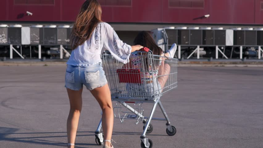 SLOW MOTION: Girls playing with shopping cart. Two young women spinning and playing with pushcart on an empty parking lot.