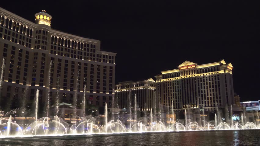 Las Vegas, Nevada - April 2018: Bellagio fountain water show at night in Las Vegas. Fountains at Bellagio Hotel and Casino in Las Vegas. Musical Fountains. 4k video with night panoramic shooting.