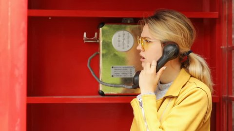 Beautiful young girl talking on the phone from the payphone disappointed sad worried woman using public telephone calling booth english britain old-fashioned style of communication on distance