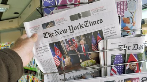 PARIS, FRANCE - JUNE 13, 2018: The New York Times on stand newspaper at press kiosk on cover U.S. President Donald Trump meeting North Korean leader Kim Jong-un in Singapore  woman walking slow motion