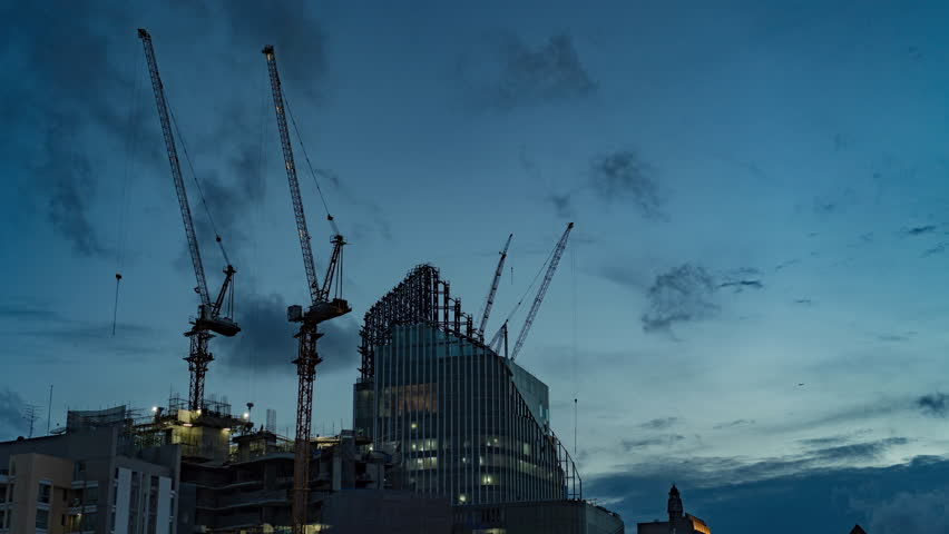 Timelapse Construction the buildings. Construction Process of Skyscraper  with cranes on the roof and clouds on a blue sky. Day to Night Time lapse 4K.
