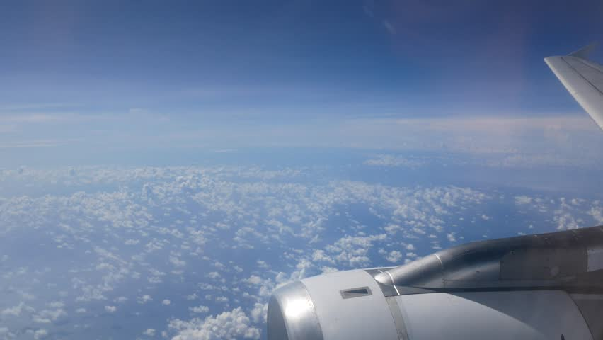 View of the sky above cloud level from the cabin window of airplane (plane) flying in the sky in clear day with some cloud (look through plan window with reflection,See plane engine and wing)-4K UHD #1012296233