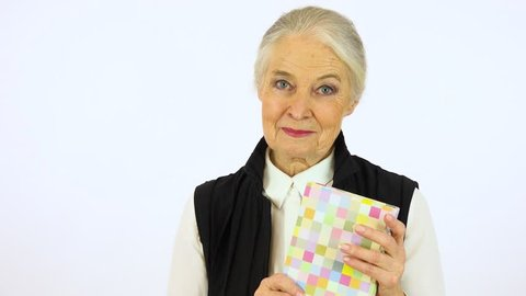 An elderly woman holds a book, smiles at it and at the camera - white screen studio