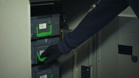 Bank employee opening ATM safe, taking out bundle of dollars, cash-in-transit
