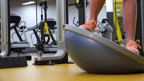 A fit woman trains on a bosu ball in a gym - closeup on the ball