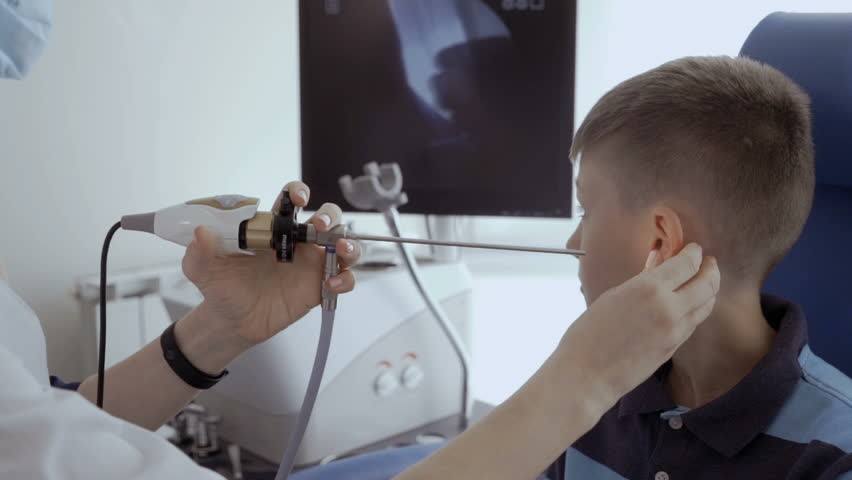 Doctor check ear of child with ENT telescope