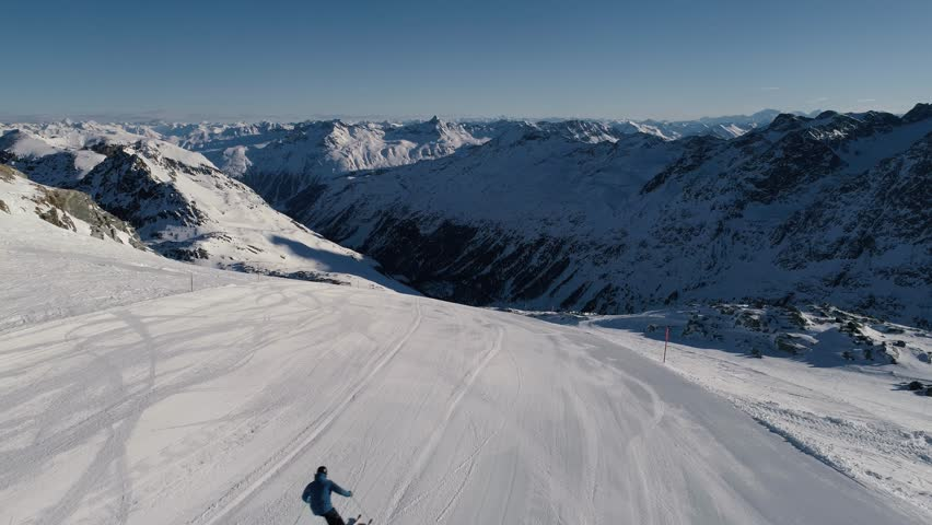 Aerial view of a skier going down a wide open and empty slope early in the morning in the alps. | Shutterstock HD Video #1012327883