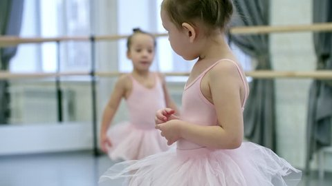 Medium shot of timid little girl in pink leotard and tutu skirt feeling uncomfortable in her first ballet lesson, other girls walking around the room in the background