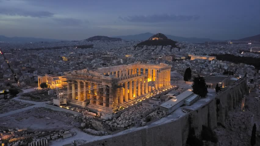 Athens Acropolis and Parthenon in evening in 4k drone shot. City center in background