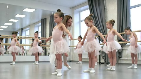 Young female ballet teacher correcting mistakes of little girls in tutu skirts and leotards during dance class