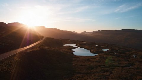 Aerial view on The Faroe (Føroyar) Islands (Denmark). Flying with drone following a car with sunset in the mountains.