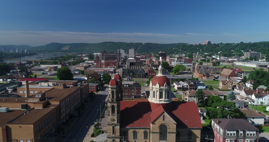 A slow forward aerial establishing shot (DX) of the small rust belt Ohio town of Steubenville. St Peter Church in the foreground. Barges on the Ohio River in the distance.