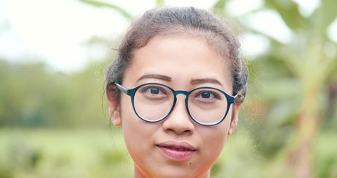 Close up asian girl portrait face.Have a smiley face with wear glasses and nature background