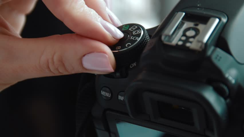 Hand holding and setting up a digital SLR camera. Close up of photographer hands on a photo camera on the set ot production shoot.   Shutterstock HD Video #1012398593