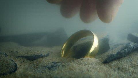 Someone Picks Up Gold Ring Underwater