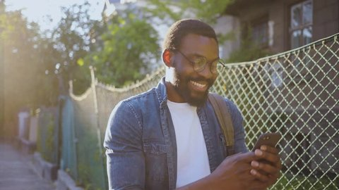 Close up african american young attractive man glasses using phone walk on street smile sunlight sunset cellphone computer fashion internet face outside technology businessmen black young city mobile