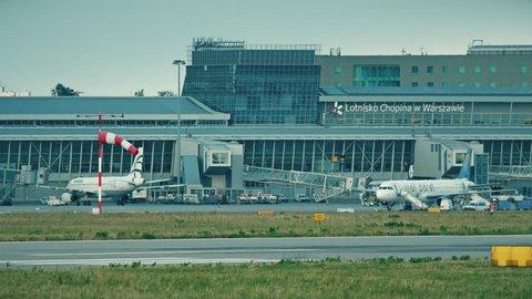 WARSAW, POLAND - JUNE 15, 2018. Passengers board airplane via jetbridge at Chopin airport terminal
