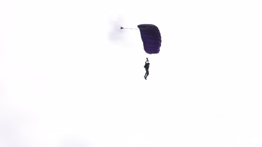 A military paratrooper falls on a parachute. Cloudy sky. 4K, Panning, 50fps, UHD.